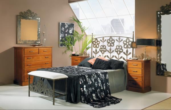 Habitación amueblada con cama vestida en el centro y cabecero de forja de flores margaritas