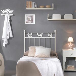 Habitación amueblada con mobiliario basado en mariposas y colores pastel con cabecero de forja de mariposas