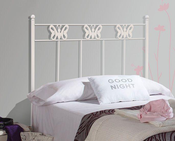 cama hecha con la ropa en colores claros y un cabecero de cama de forja decorado con mariposas