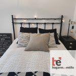 habitación con cama simple vestida con cojines y cabecero de forja negro